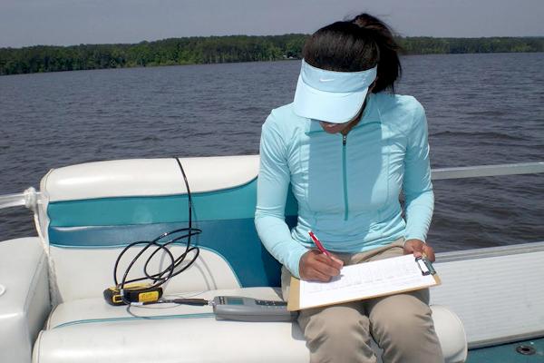 Lauren Lowman measures temperature, conductivity and salinity with a conductivity/temperature meter at Jordan Lake (near Durham, North Carolina). (Credit: Lauren Lowman)