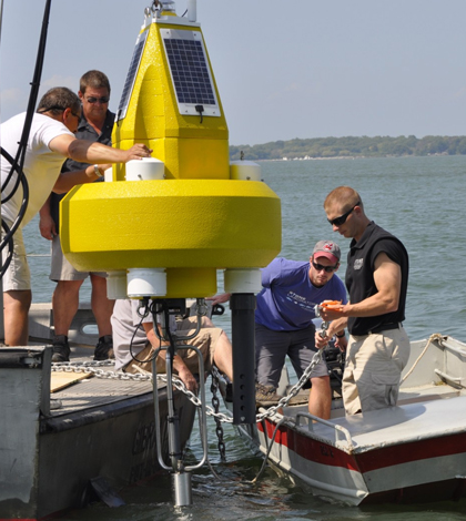 Dr. Justin Chaffin prepares to deploy a data buoy in Lake Erie. (Credit: Ohio Sea Grant)